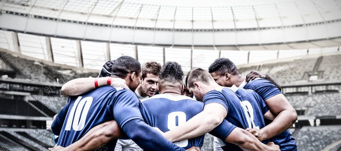 Digital composite image of team of rugby players standing in a huddle in sports stadium