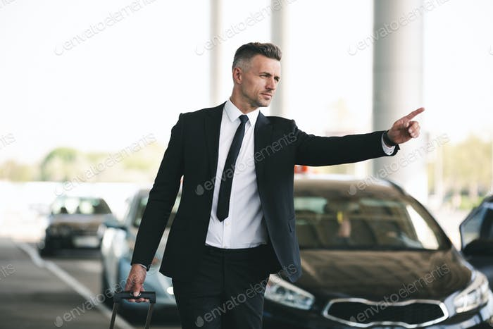 Confident mature businessman catching a taxi