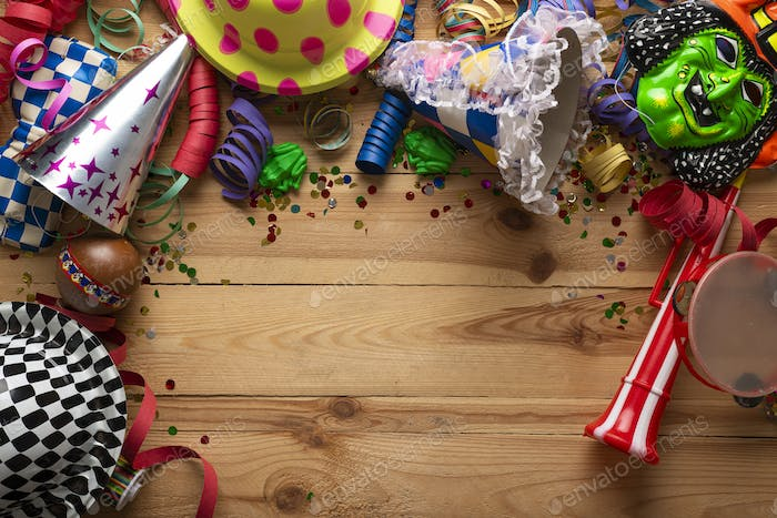 Carnival background on a wooden surface. Masks, coiled streamers, confetti and many more