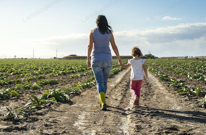 Frau Bauer und kleines Mädchen zu Fuß auf der Landwirtschaft Land.