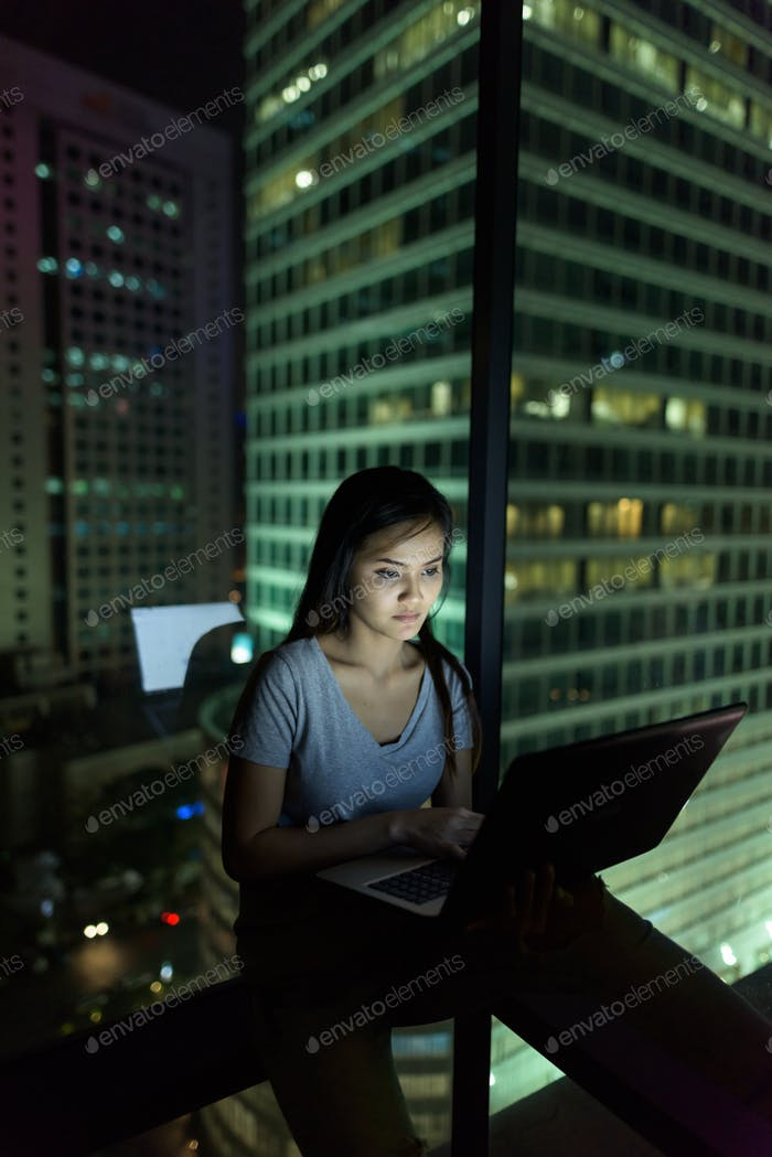 Young beautiful Asian woman using laptop against glass window wi
