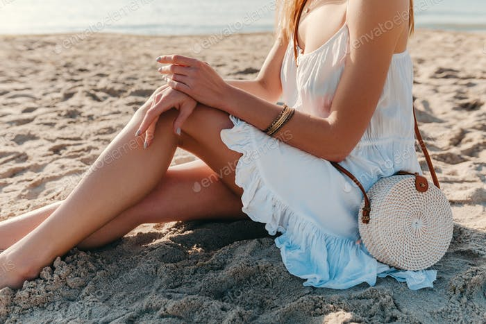 woman in white dress with straw purse bag summer style on beach accessories