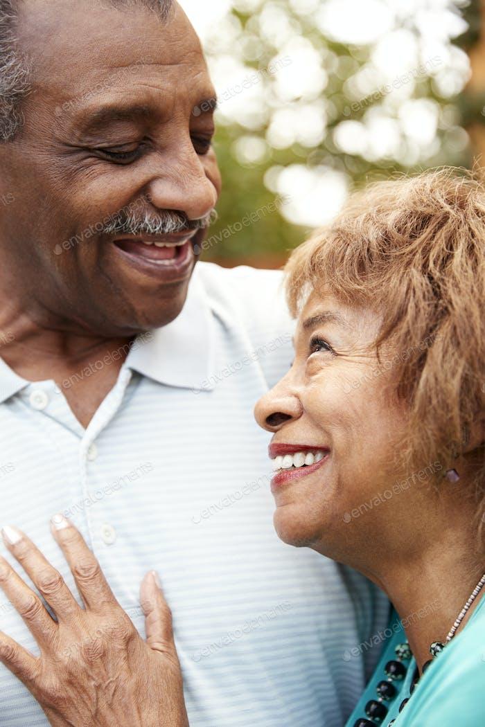 Senior black husband and wife embracing, close up, vertical