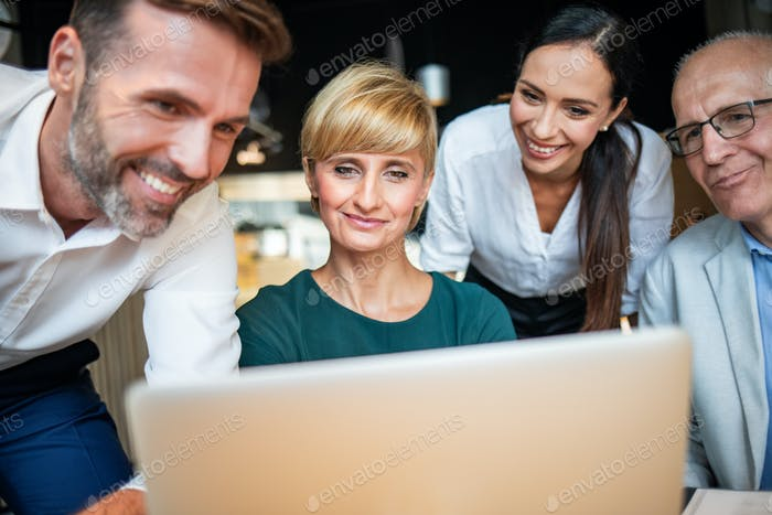 Business people looking at laptop at cafe and discussing