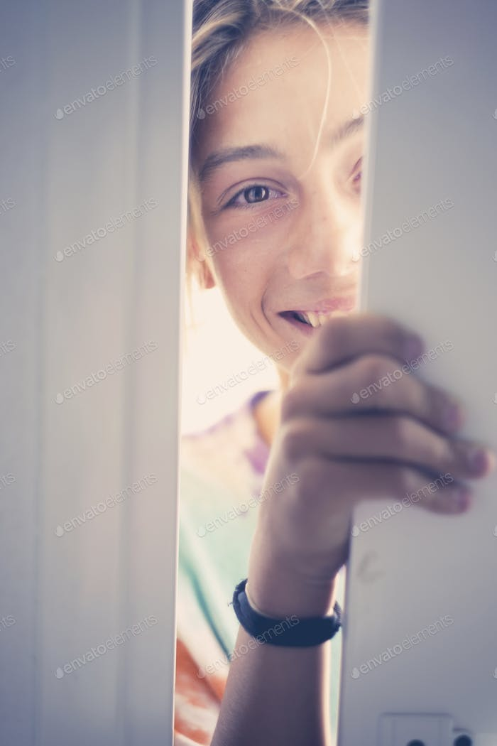 Cheerful young teenager opening a door and smile