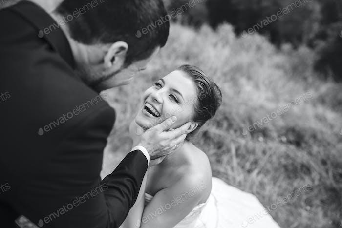 Bräutigam berührt sanft das Gesicht seiner Braut