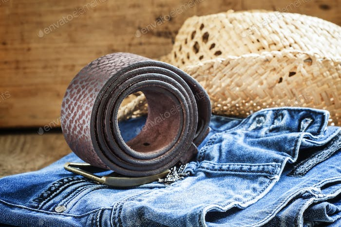 Jeans, straw hat, leather belt - women's clothes in cowboy country style