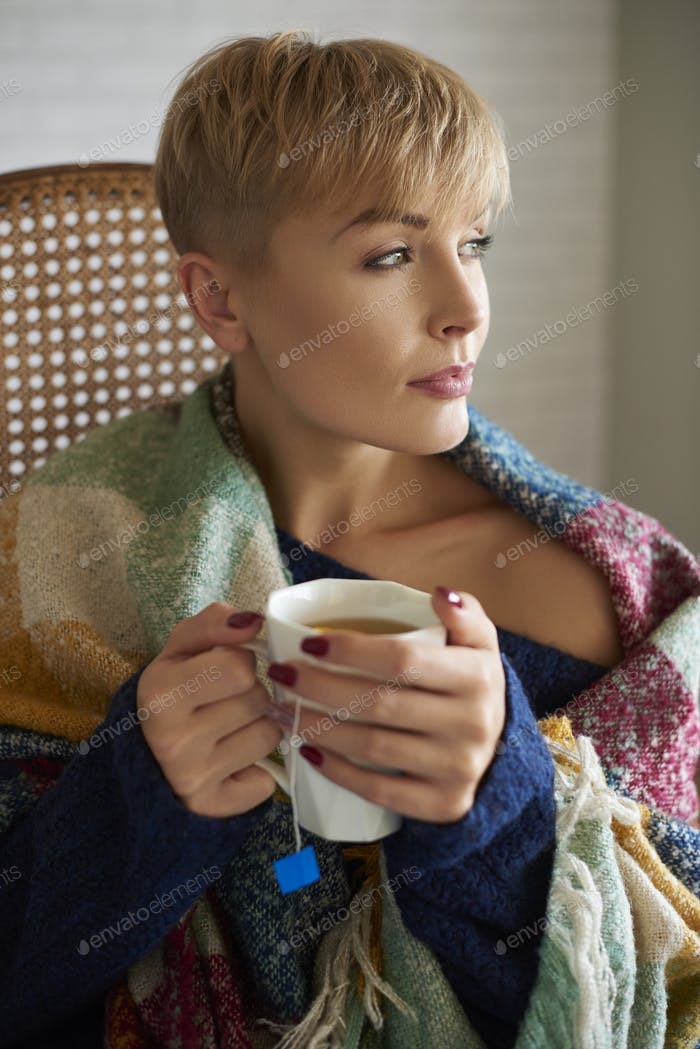 Woman wrapped in a blanket drinking hot tea