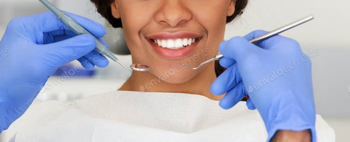 Beautiful female smile and dentist hands with tools