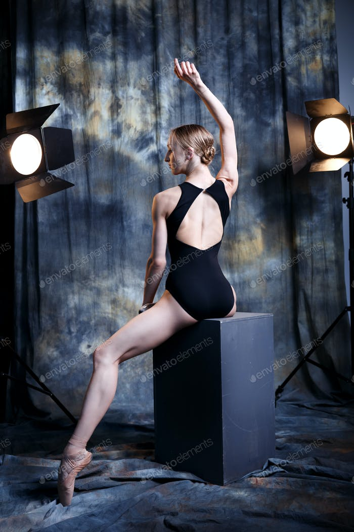 Young ballerina in a dark studio