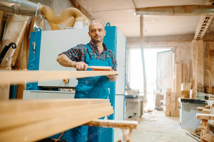 Carpenter processes board on plane machine
