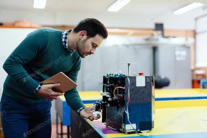 Junger Ingenieur testet seinen Roboter in der Werkstatt