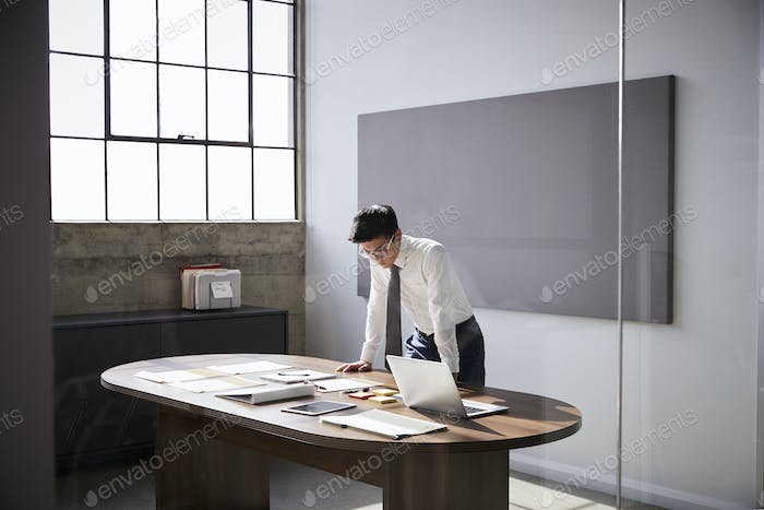Businessman standing at desk working alone in an office