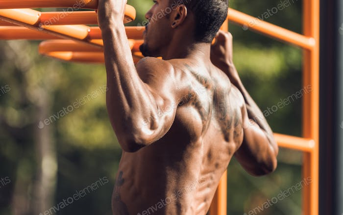 Muscular man doing pull up on horizontal bar