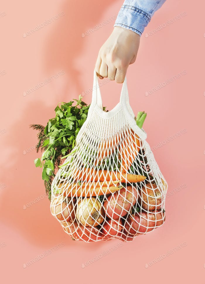 Mesh bag with vegetables and herbs in female hand. Woman hold string net shopping bag