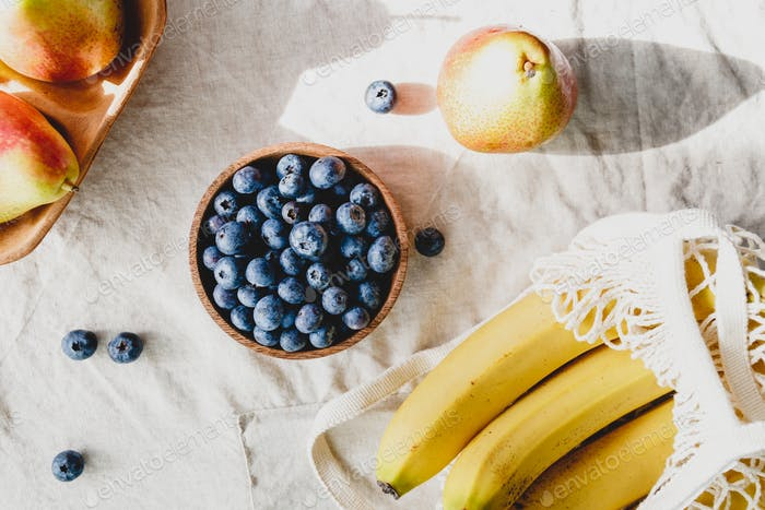 Bananas in a net bag, pears and blueberry