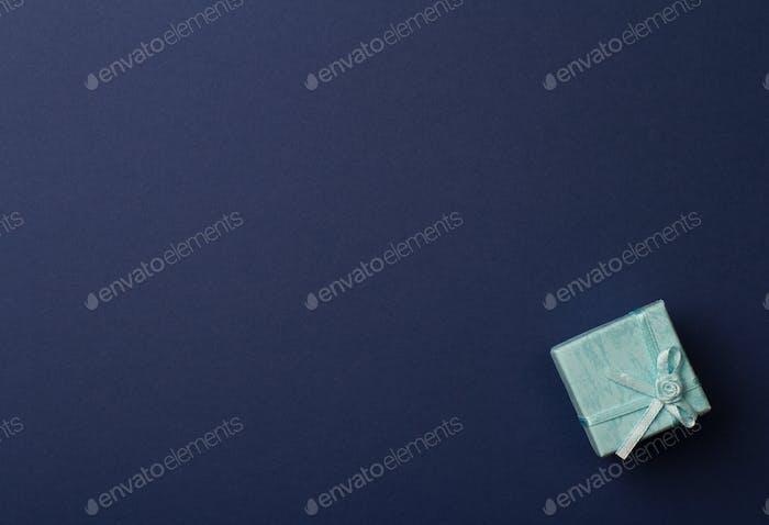 kleine Geschenkbox auf dunkelblauem Papierhintergrund