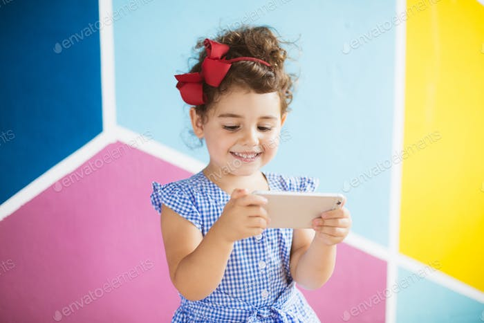 Cute smiling baby girl with dark curly hair in blue dress happil