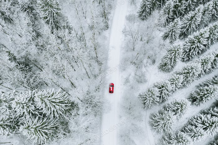 Luftaufsicht des schneebedeckten Waldes mit Winterstraße und rotem Auto.