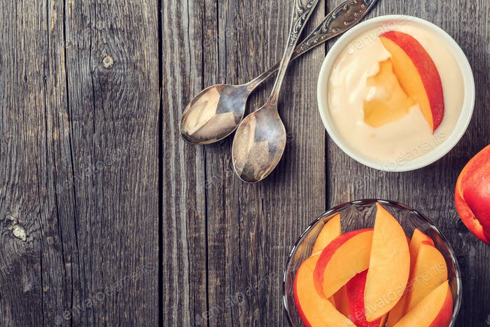 Homemade yogurt with fresh peaches on a wooden background.