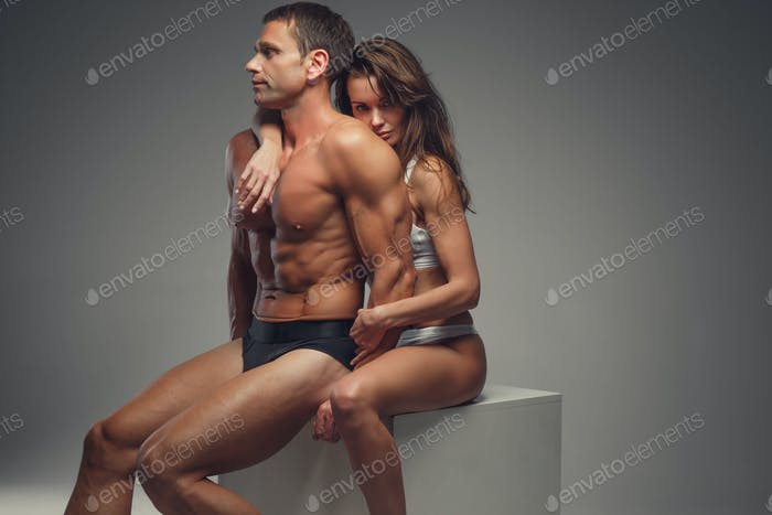 Naked athletic couple posing in studio.