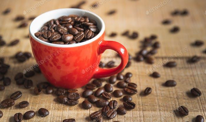 Eine Tasse voller Kaffeebohnen auf einem hölzernen MangoCouchtisch