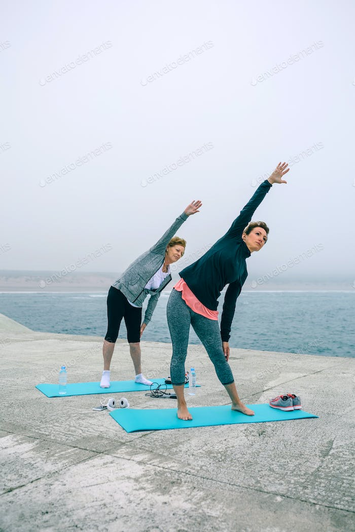 Senior woman with coach stretching side