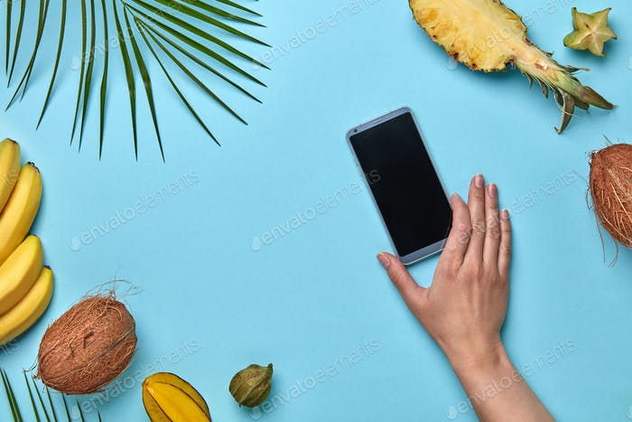 A woman's hand holds a mobile phone against a blue background around a tropical fresh fruit with