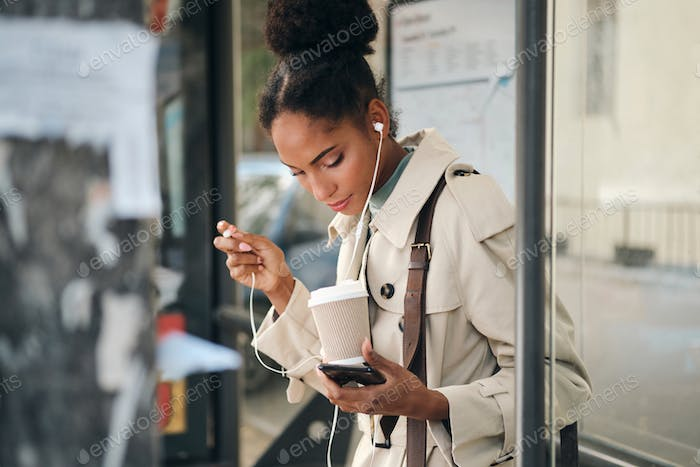Beautiful African American girl in stylish trench coat with coffee and cellphone at bus stop