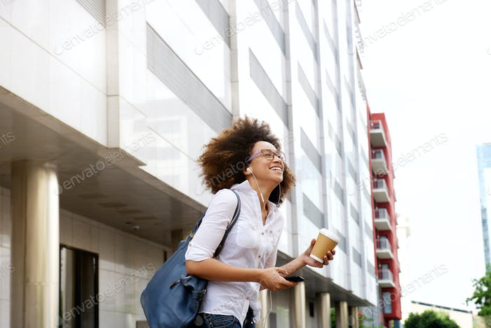 Smiling african female student walking with cellphone