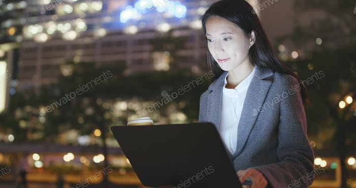 Junge Geschäftsfrau arbeitet nachts am Notebook-Computer