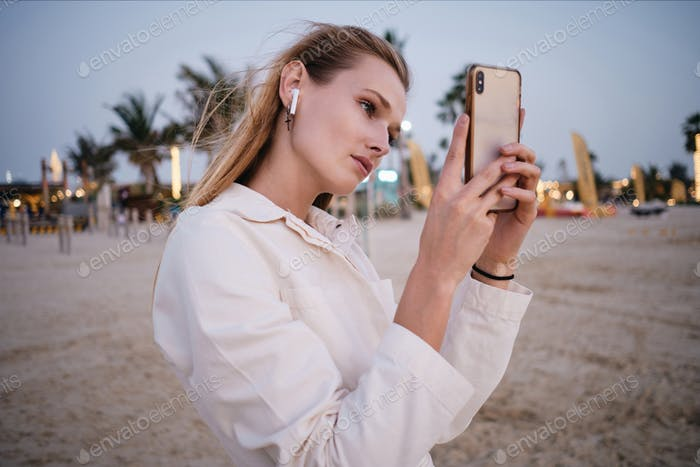 Attractive girl with wireless earphones dreamily taking photos on cellphone on beautiful beach