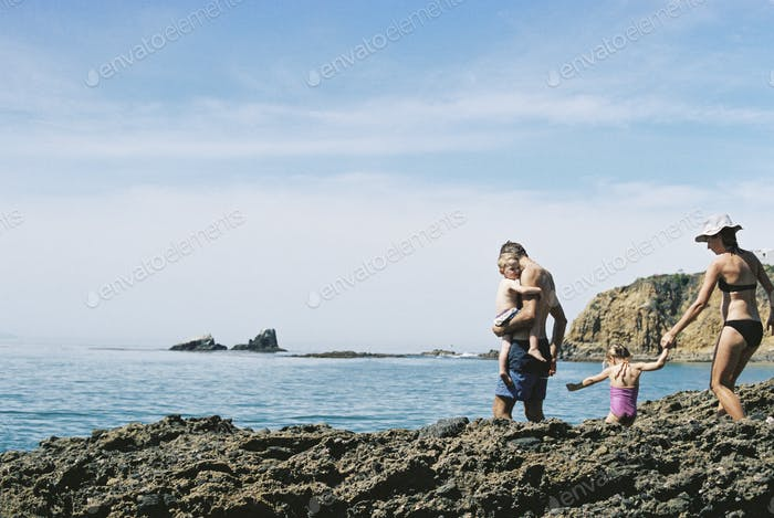 A family on holiday, two adults with their son and daughter walking across rocks by the ocean.