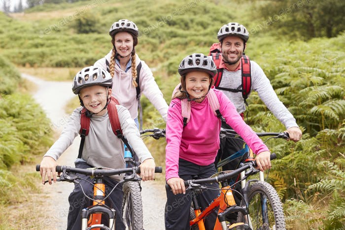 Portrait of parents and children sitting on mountain bikes, smiling to camera