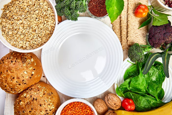 Selection food rich in fiber on white wooden background around empty plate