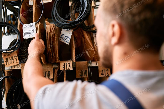 Worker Choosing Parts in Storage Room