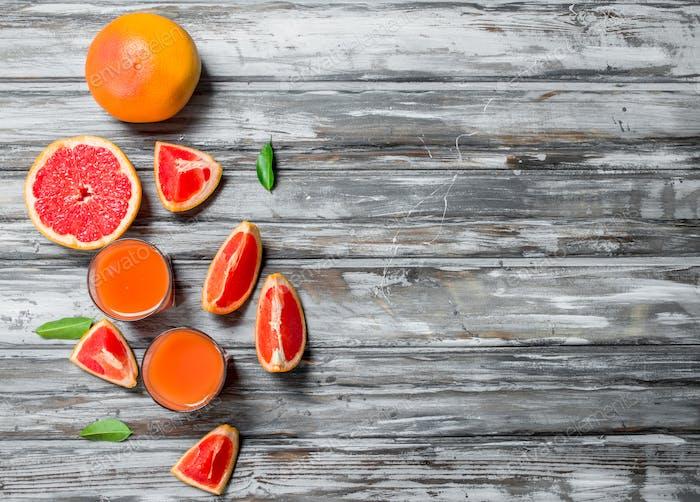 Grapefruitsaft in einem Glas und Stücke frischer Grapefruit.