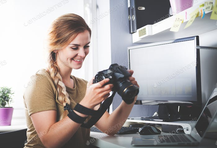 Freelance photographer woman with camera at home office editing photos