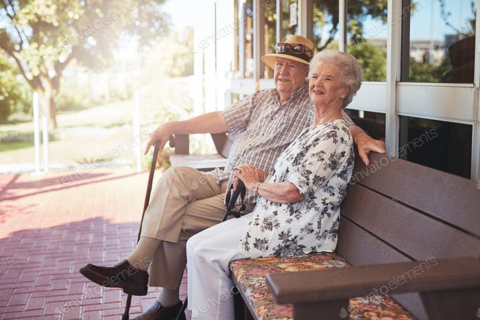 Retired couple sitting on a bench outside their home