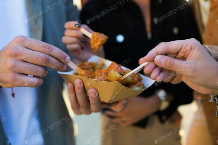 Group of friends visiting eat market and eating potatoes in the street.