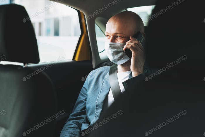 Bald man businessman in medical face mask using mobile phone inside yellow car taxi
