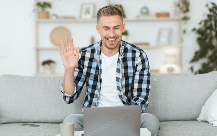 Happy guy using computer for video call and waving