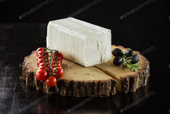 Piece of cream cheese, cherry tomatoes and olives on wooden boar