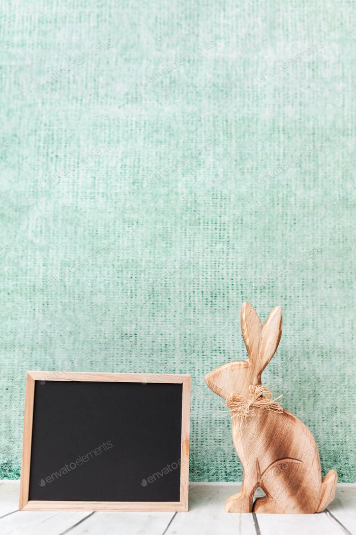 Wooden Easter holiday bunny and an empty blackboard
