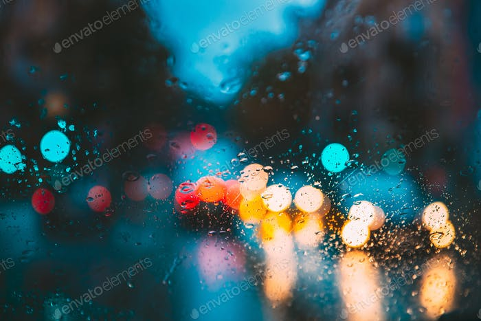 Drops Of Rain Water In Night Or Evening Street Lights On Blue Glass Background. Street Bokeh Lights