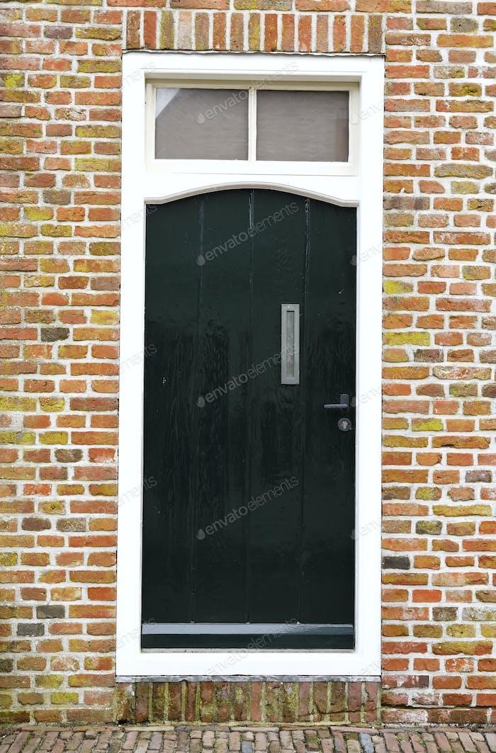 dark greed door on brick wall