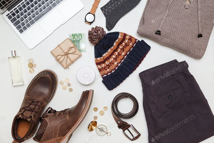 Top view of men winter outfit and accessories on wood background