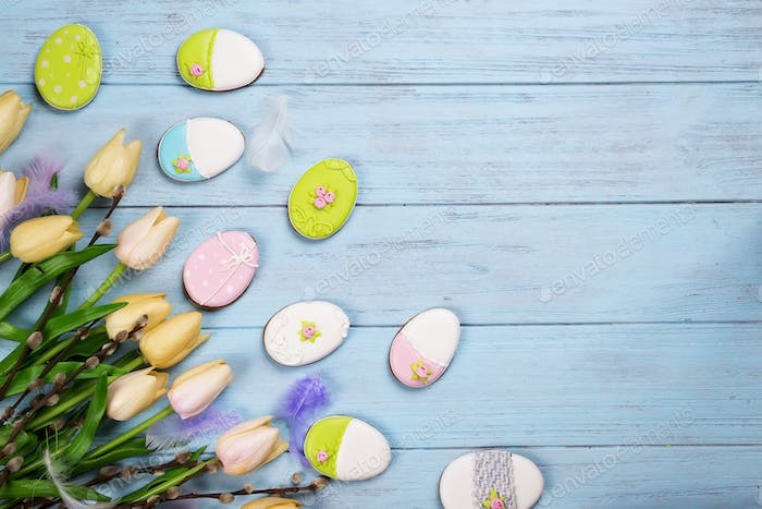Colorful easter cookies and tulips on blue wooden background