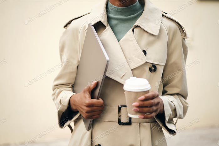 Close up casual woman in stylish trench coat with laptop and coffee to go outdoor