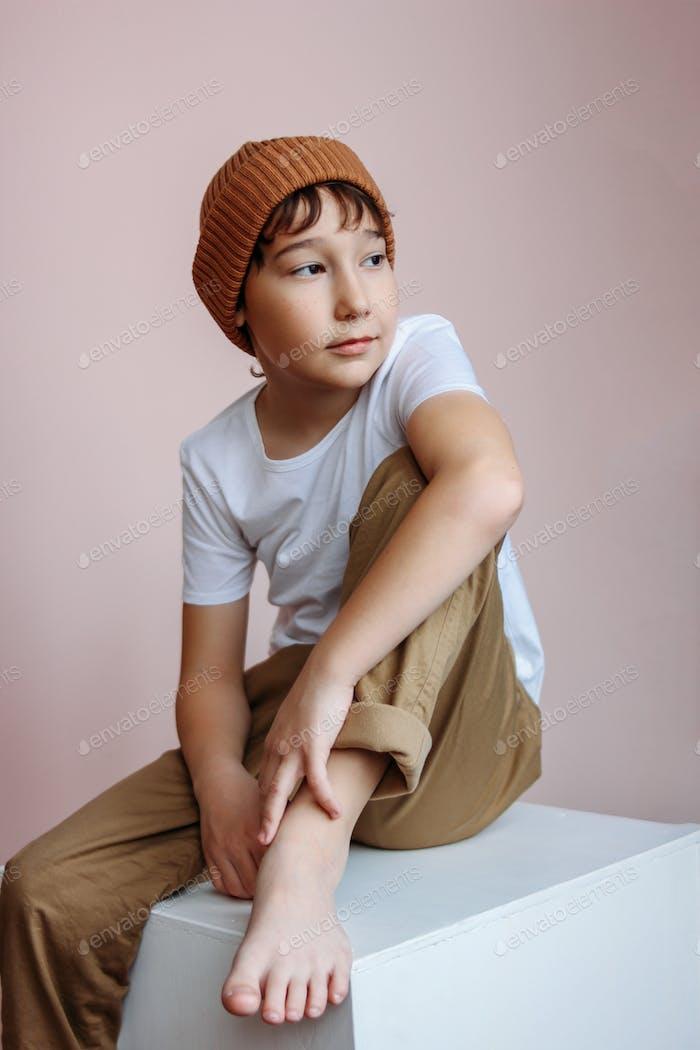 Modische attraktive Tween Junge mit dunklen Haaren in Hut sitzt auf weißen Würfel im Studio